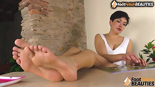 Barefoot brunette puts her long feet right in your face